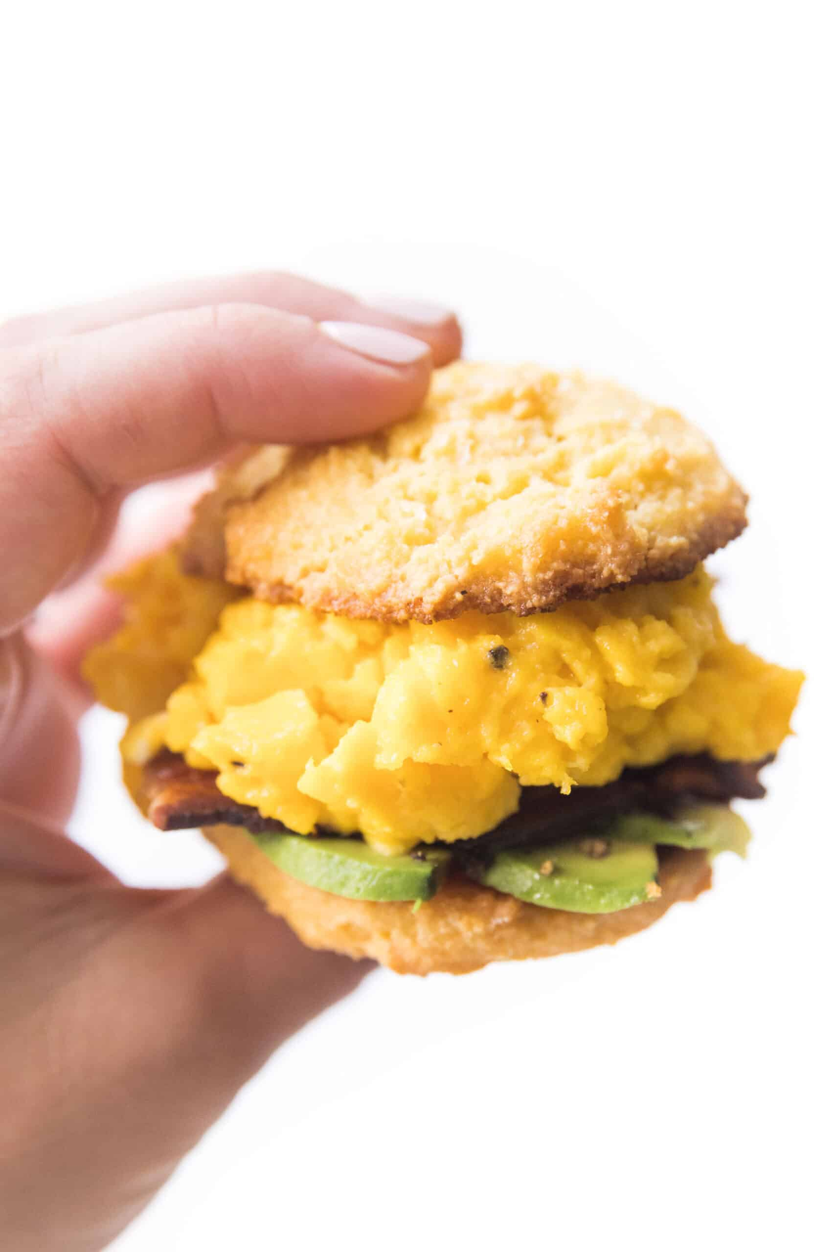 hand holding a keto biscuit breakfast sandwich with egg, bacon and avocado on a white plate and background