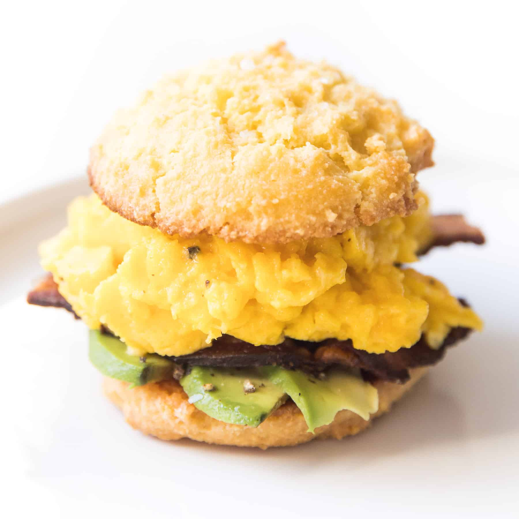 keto biscuit breakfast sandwich with egg, bacon and avocado on a white plate and background