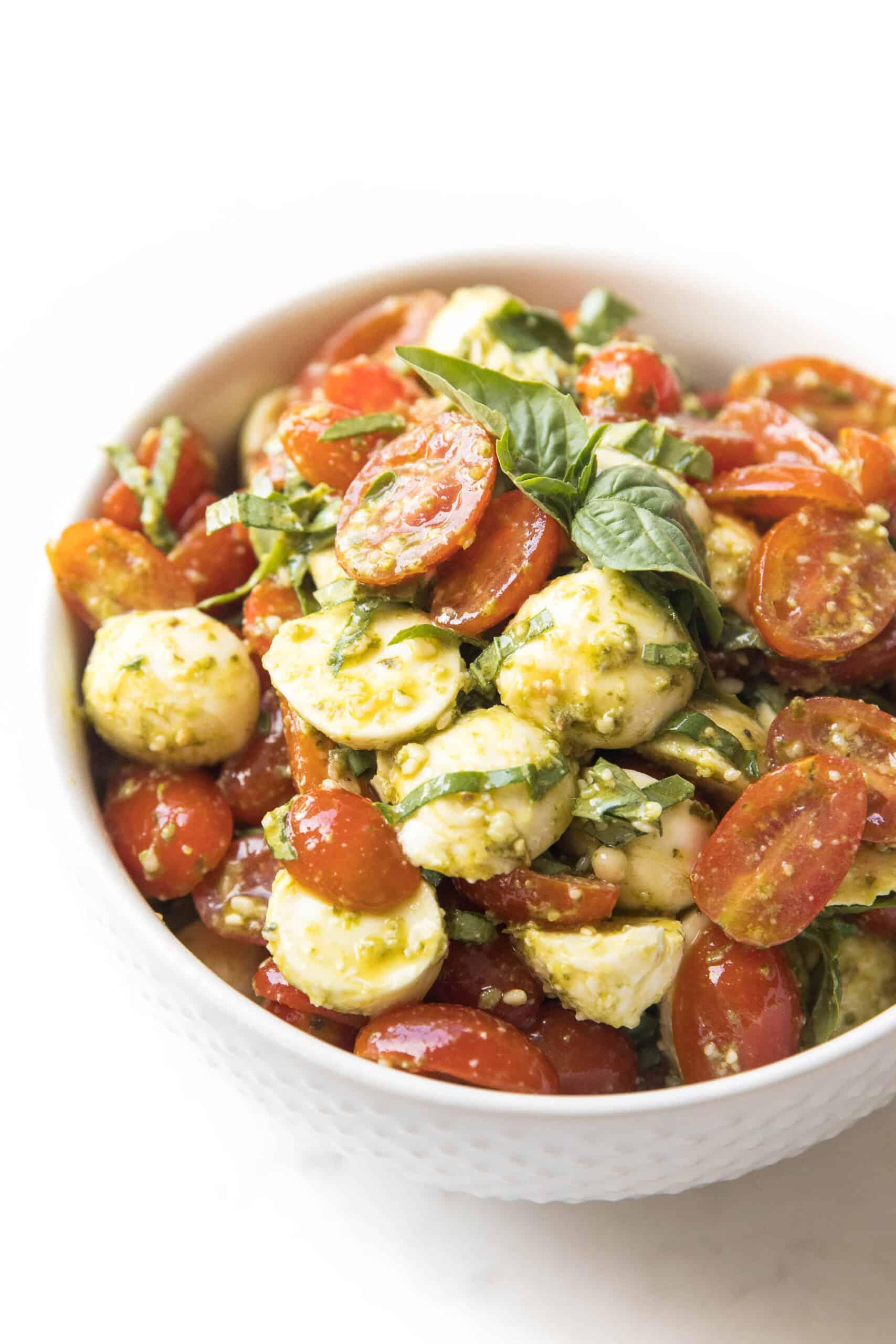 pesto caprese salad in a white bowl