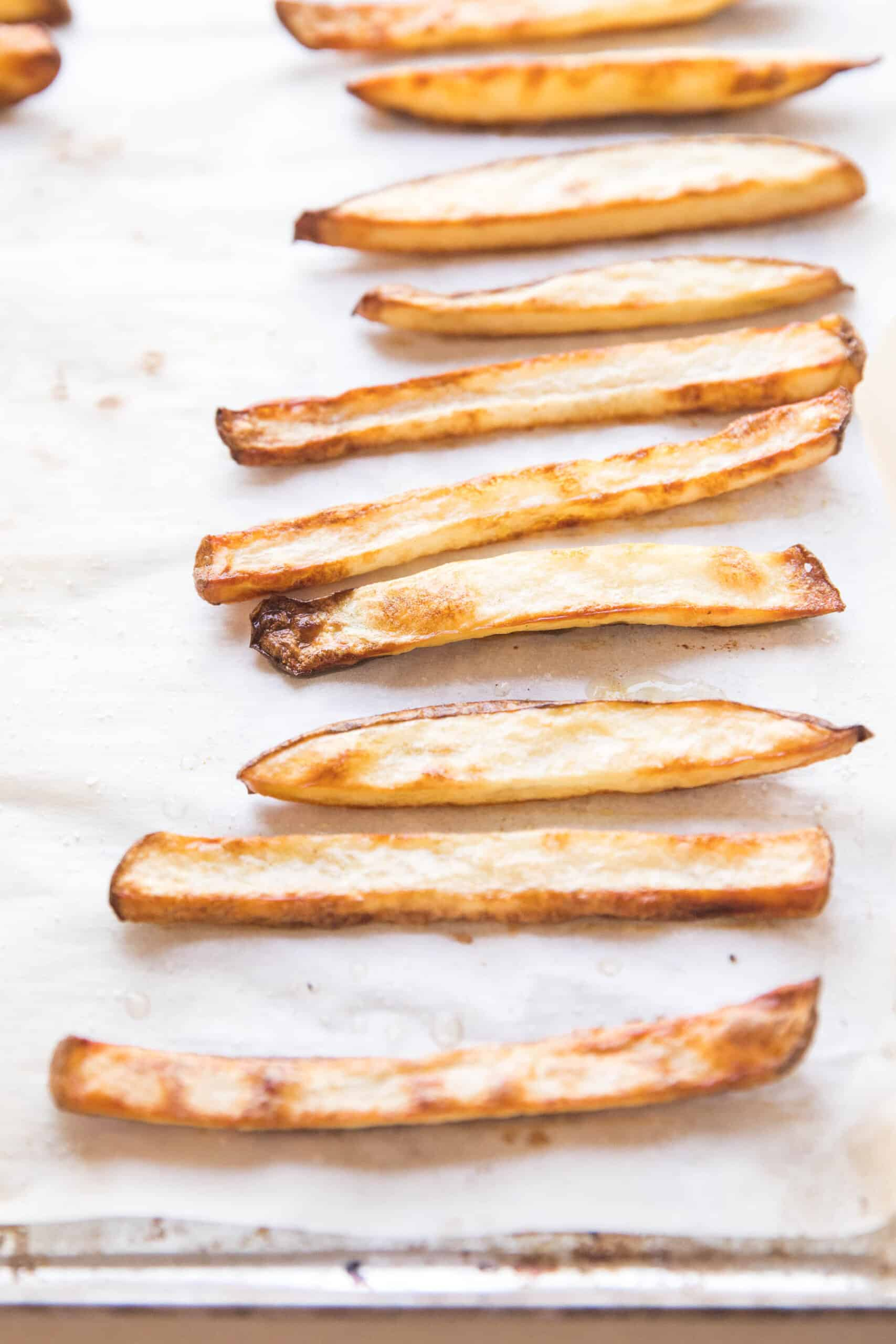 baked french fries on a rimmed baking sheet