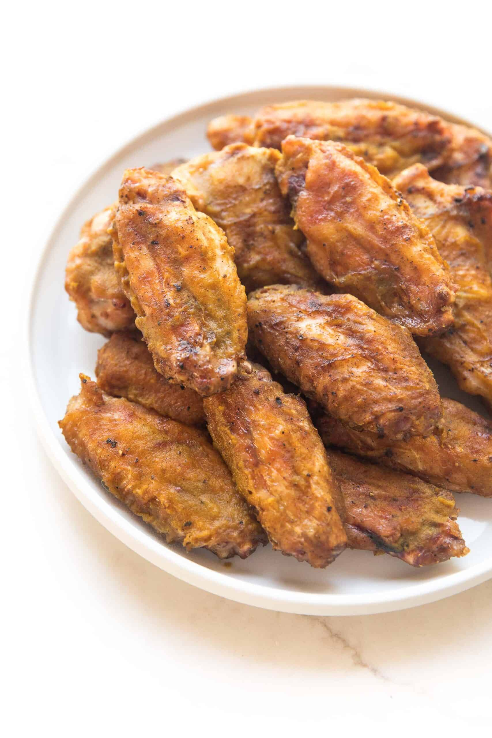 BBQ CHICKEN WINGS ON A WHITE PLATE