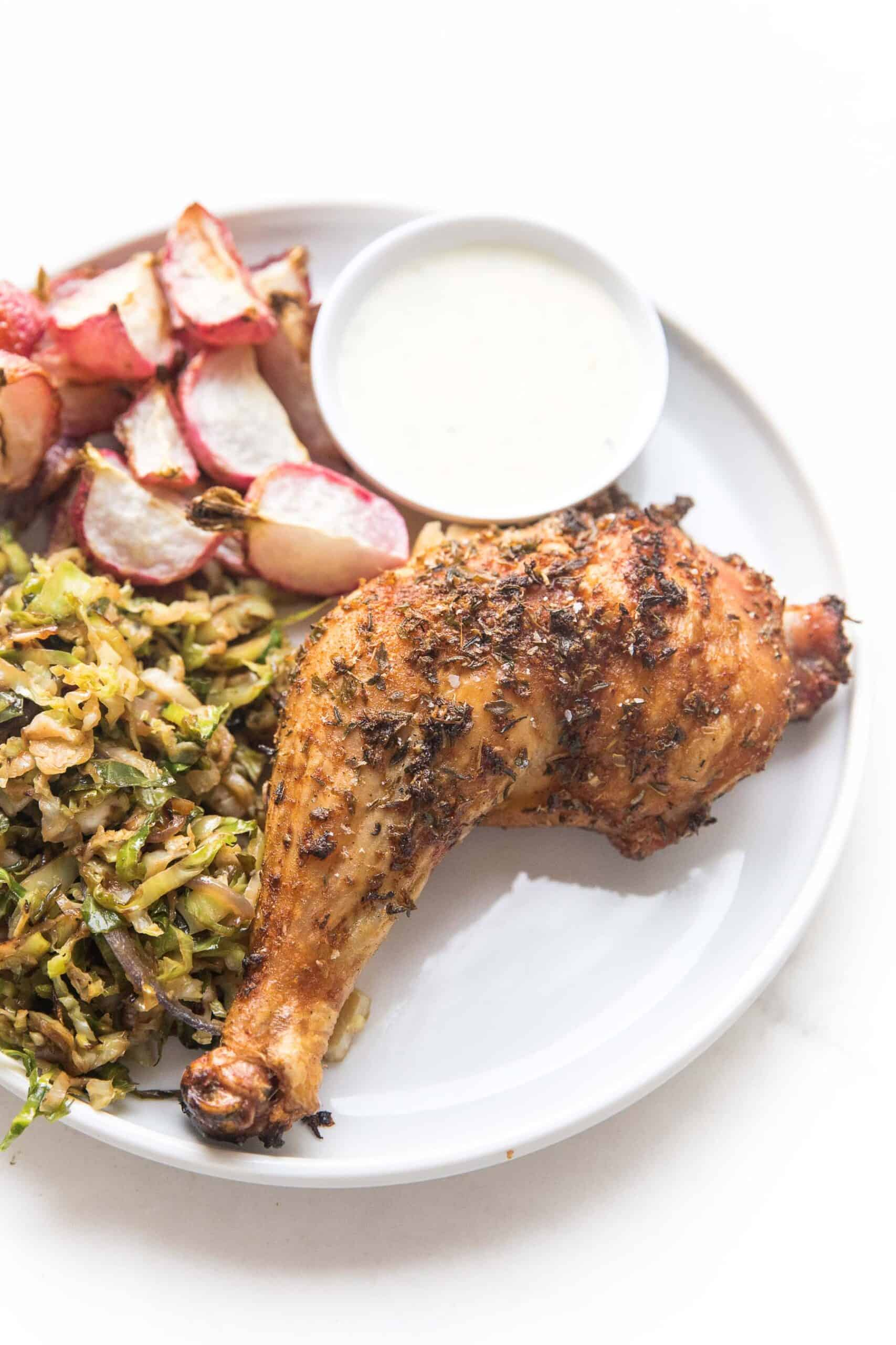grilled blackened chicken on a white place with roasted radishes and shaved brussels