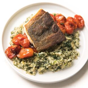 Whole30 + Keto Halibut with Spinach Artichoke Cauliflower Rice Risotto + blistered tomatoes on a white plate
