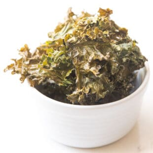 crispy kale chips in a white bowl in a white background