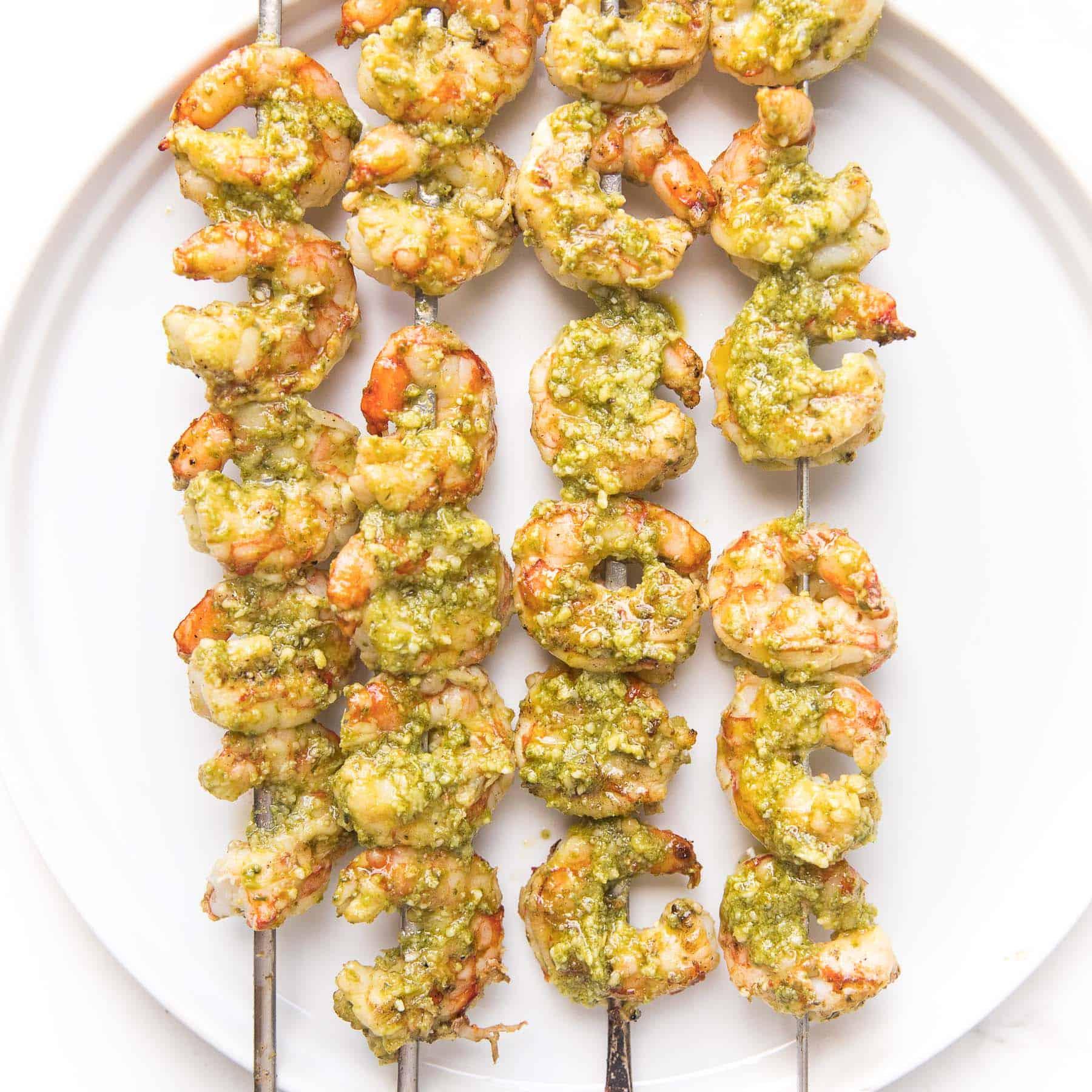 pesto shrimp kabobs on a white plate