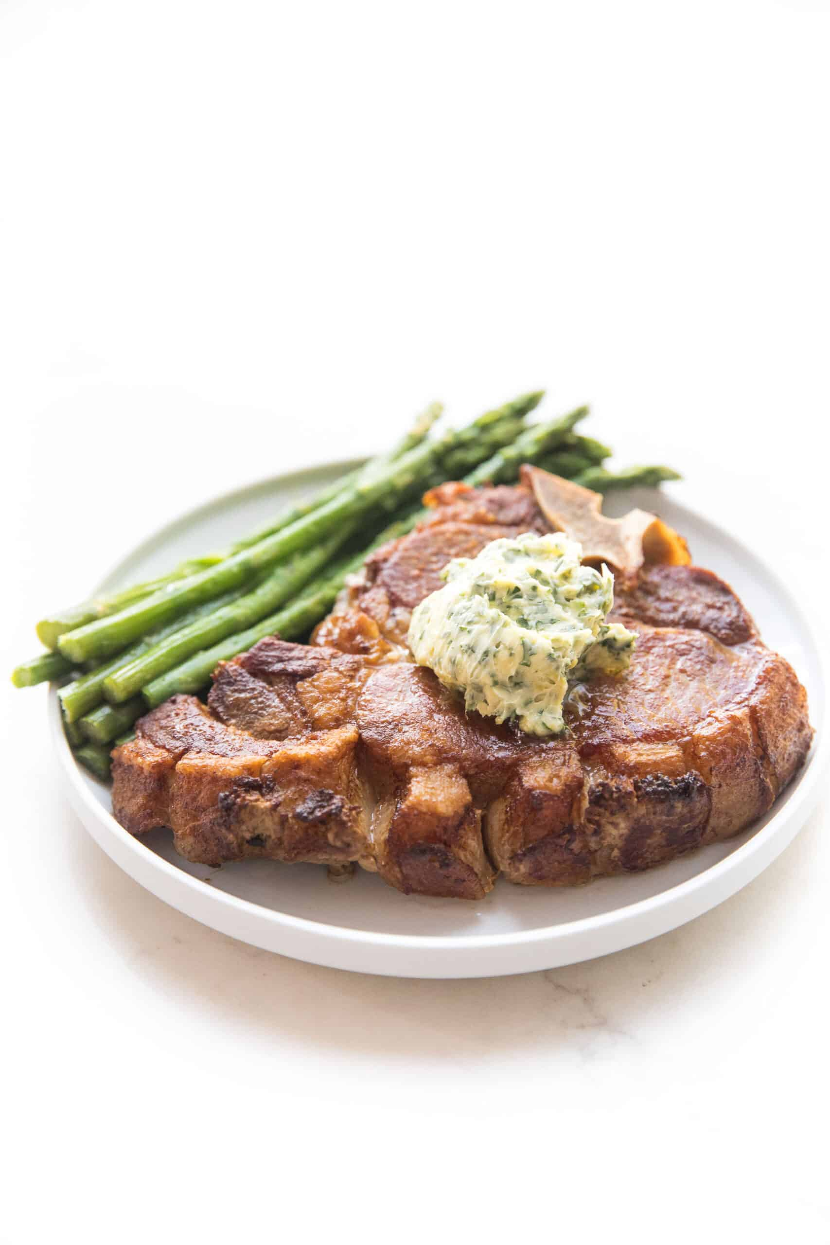 pork chop topped with herb butter with parsley and asparagus on a white plate and background