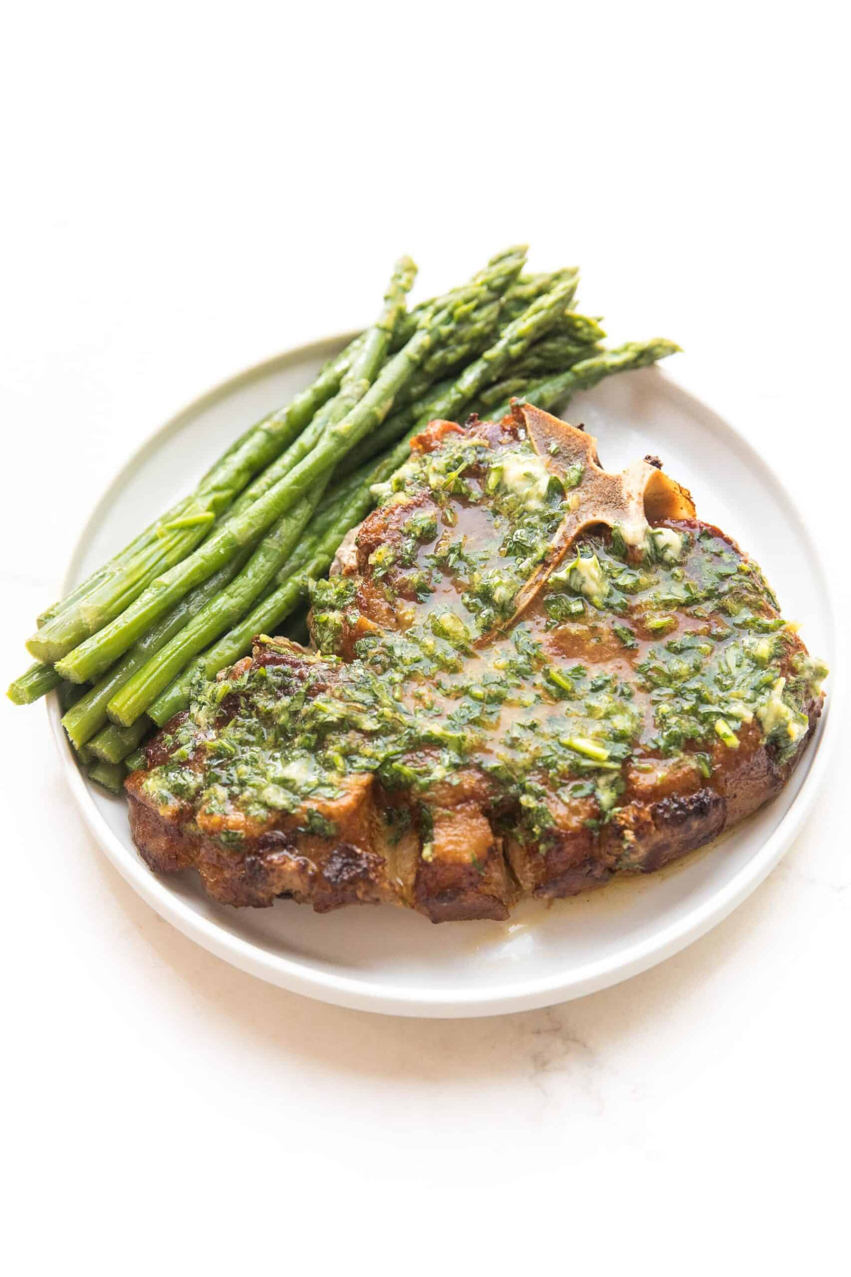 pork chop covered in melted herb butter with parsley and asparagus on a white plate and background