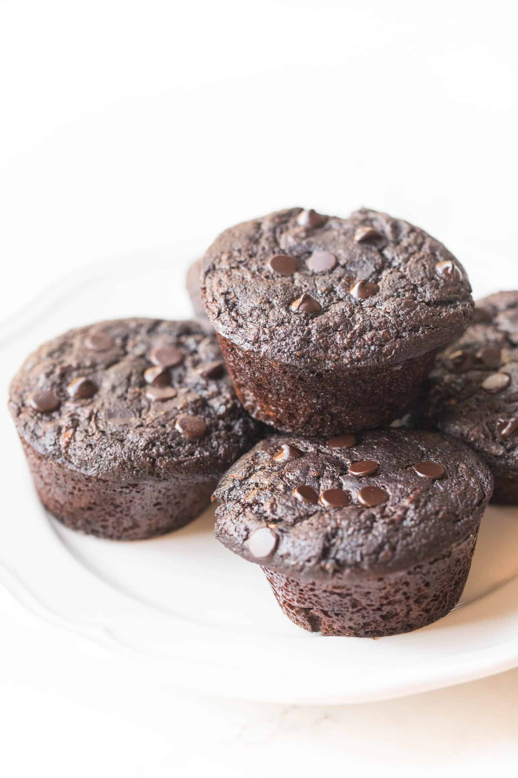 keto chocolate zucchini muffins on a white plate and background