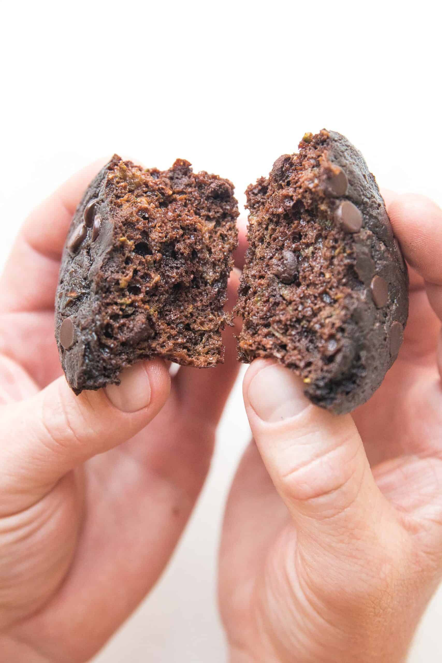hand breaking open keto chocolate zucchini muffins