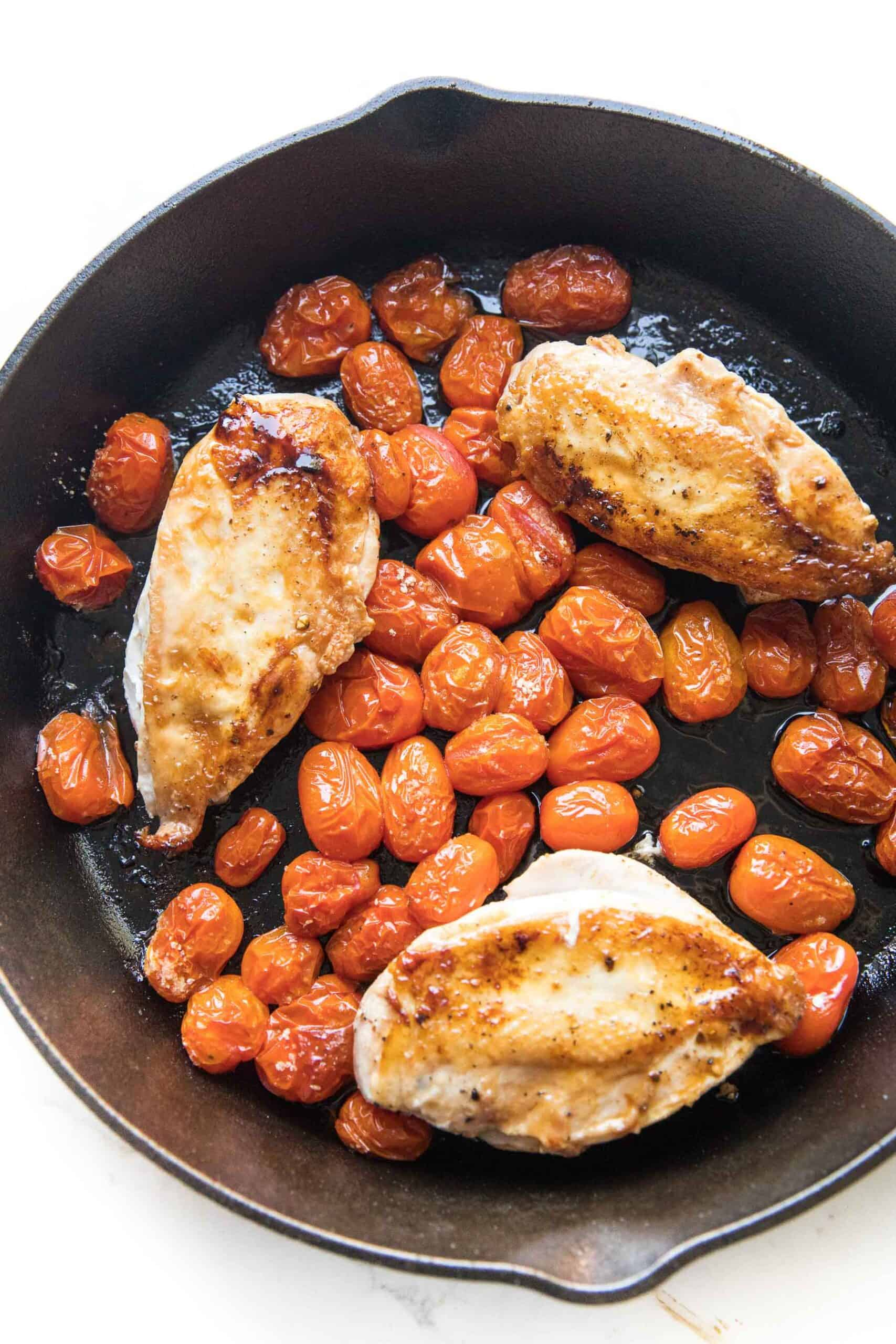 cast iron skillet with chicken and blistered tomatoes