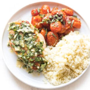 chicken with basil butter, blistered tomatoes and cauliflower rice on a white plate
