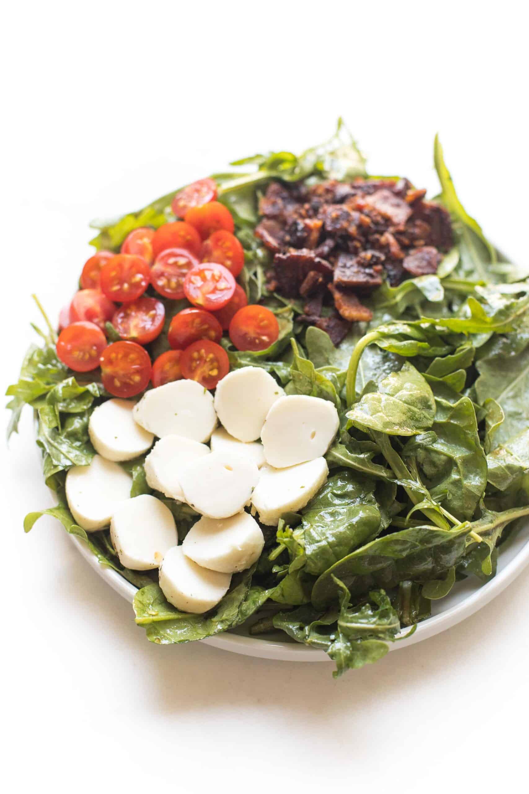 keto salad with bacon, tomatoes and mozzarella cheese on spinach and arugula on a white plate