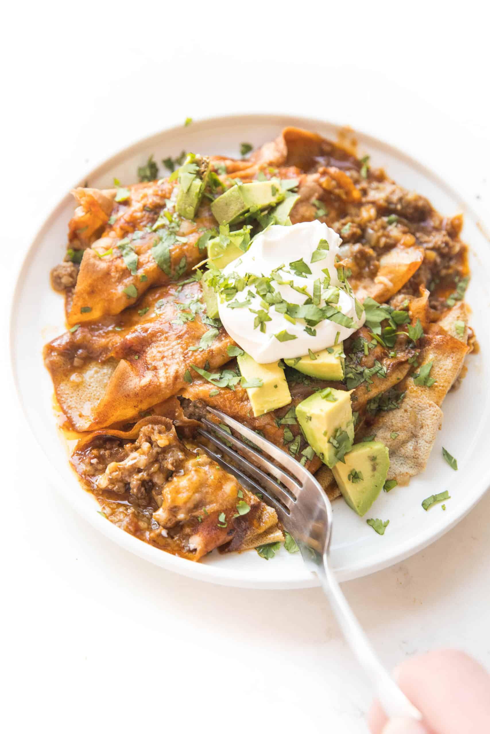 fork cutting in to keto beef enchiladas