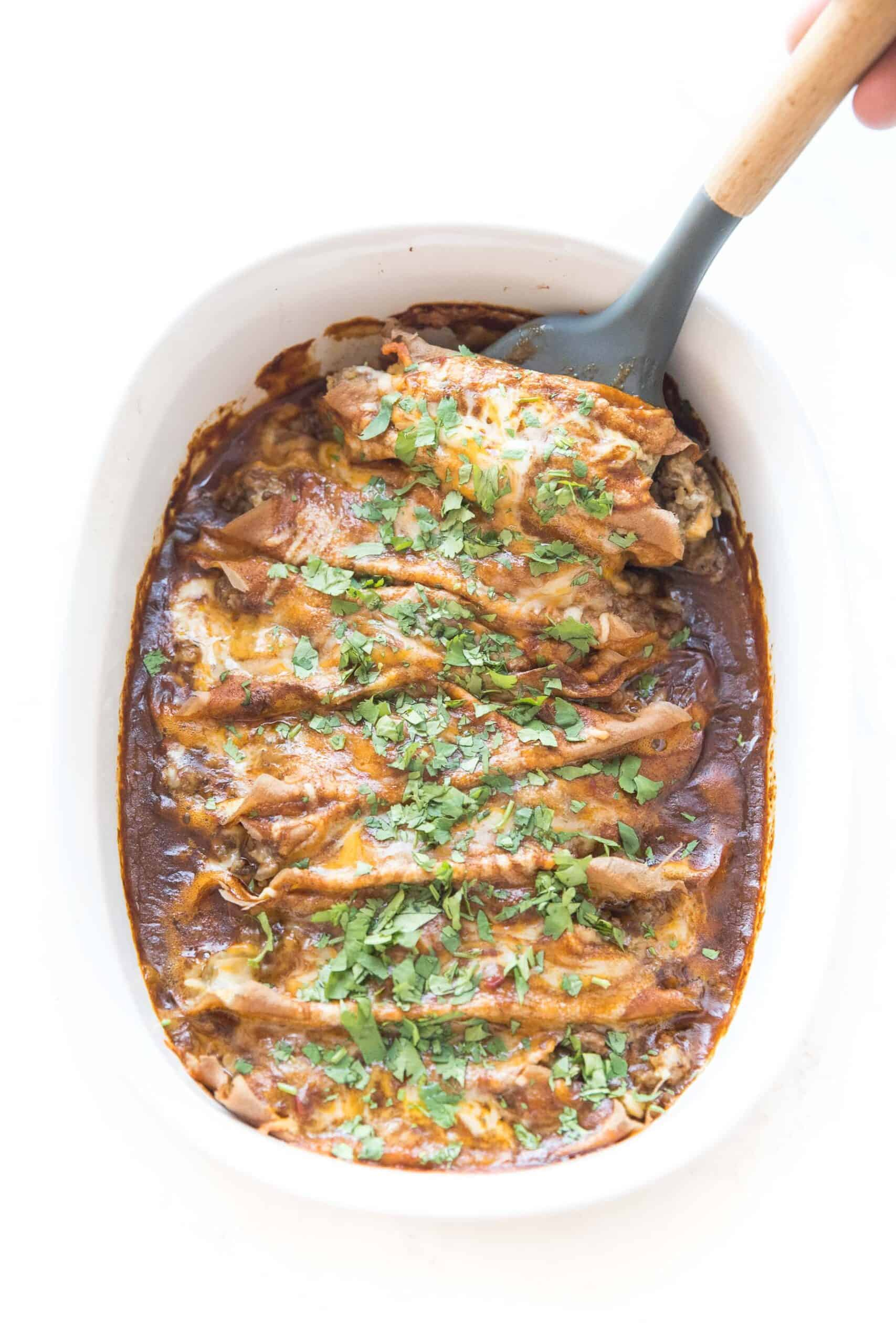 spatula scooping into keto beef enchiladas in a baking dish