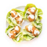 keto buffalo turkey meatballs on lettuce wraps topped with ranch dressing on a white plate and background
