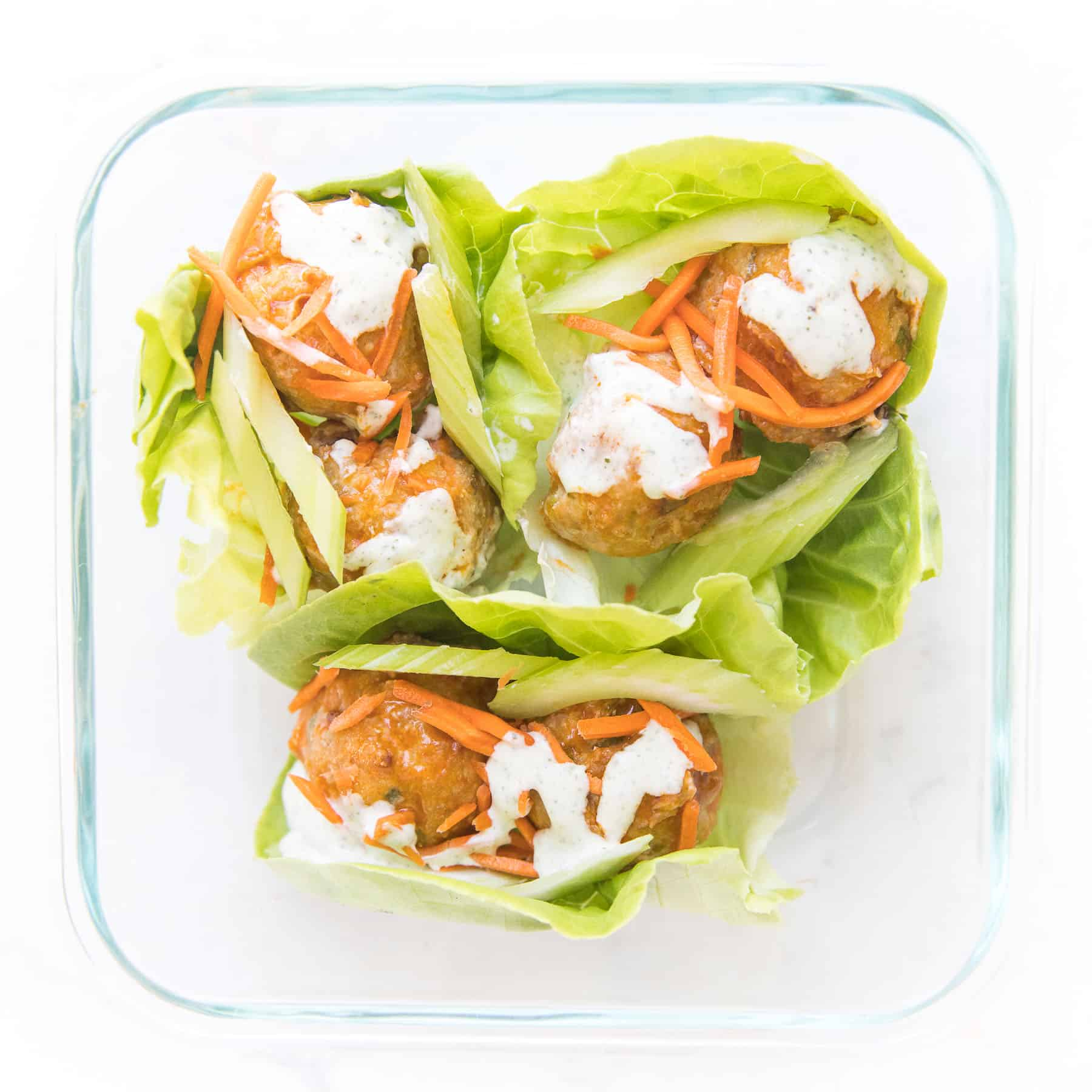 meal prep keto buffalo turkey meatball lettuce wraps in a glass meal prep container