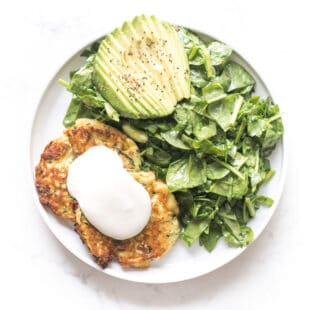 zucchini fritters topped with sour cream on a white plate and background with spinach salad + avocado