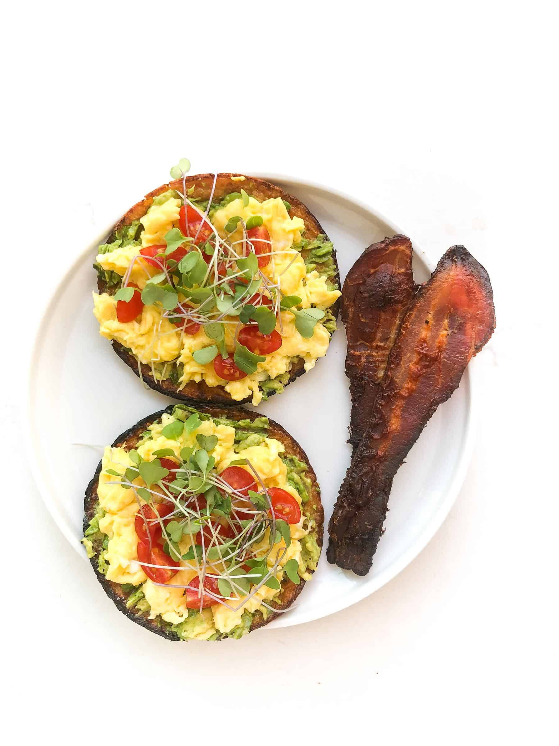 keto avocado toast topped with egg, tomatoes, microgreens and bacon on a white plate and background