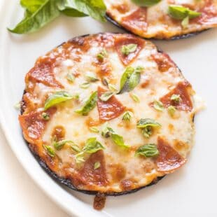 keto mini cauliflower thin pepperoni pizzas on a white plate topped with fresh basil