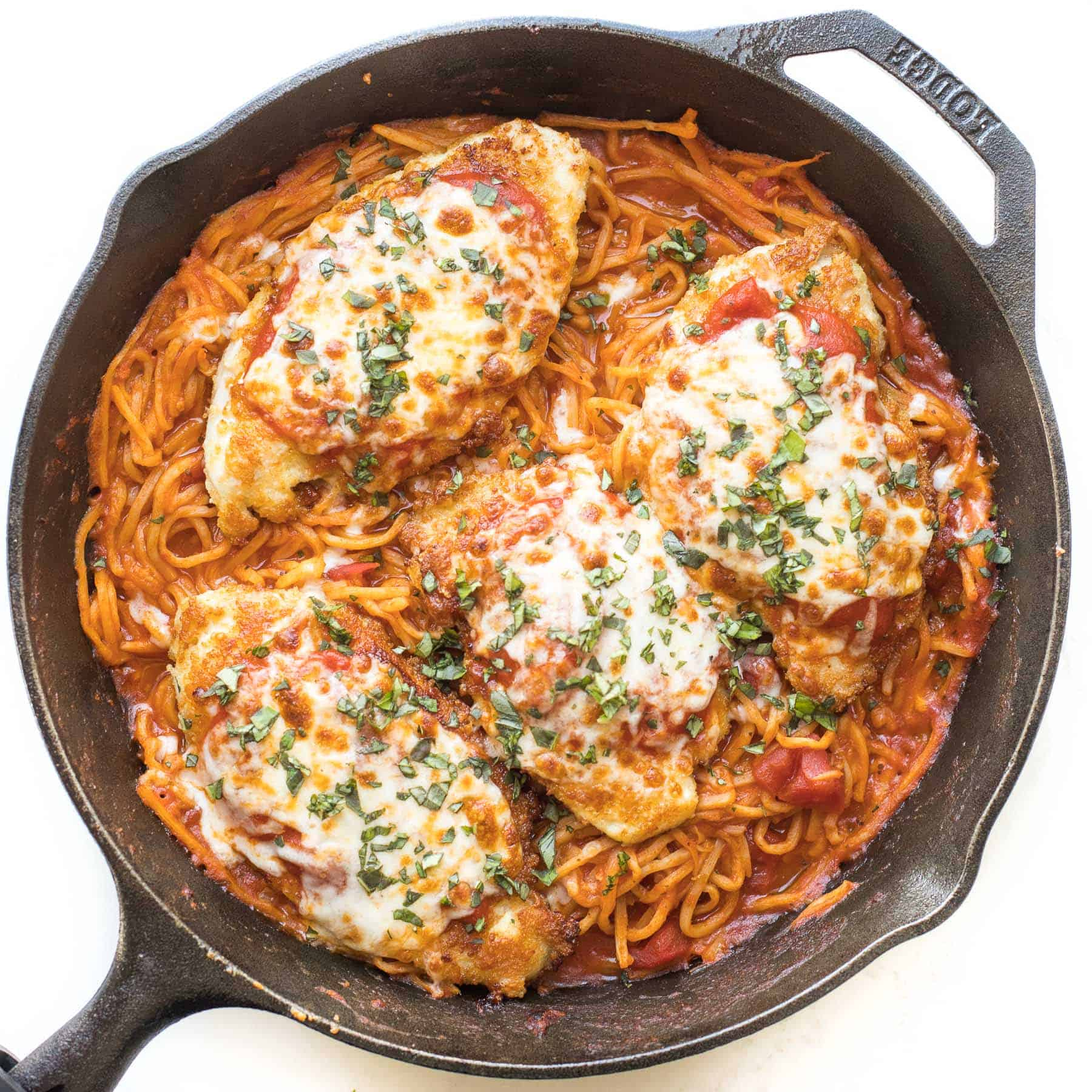 keto skillet chicken parmesan in a cast iron skillet on a white background