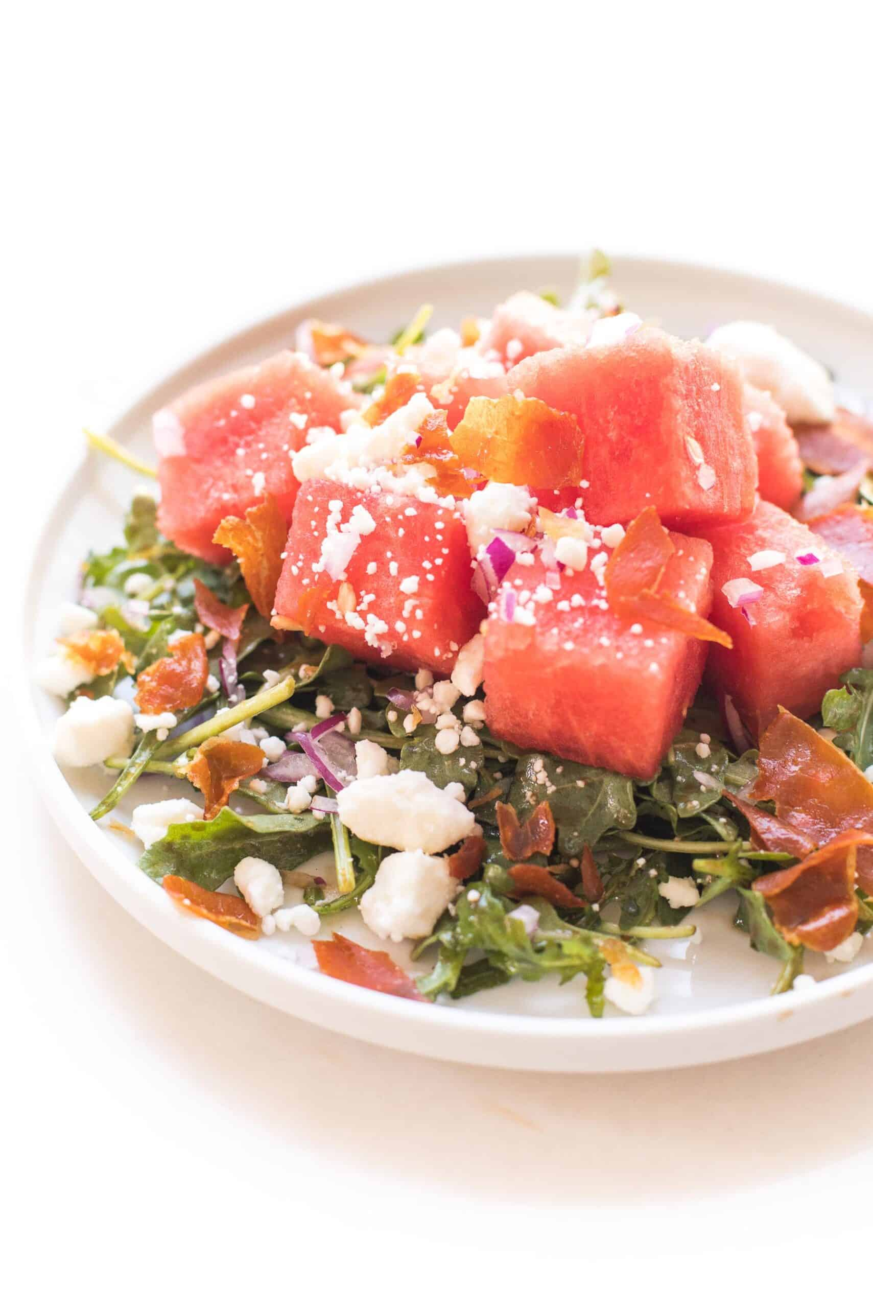 WATERMELON FETA SALAD WITH ARUGULA, CRISPY PROSCIUTTO AND RED ONION ON A WHITE PLATE