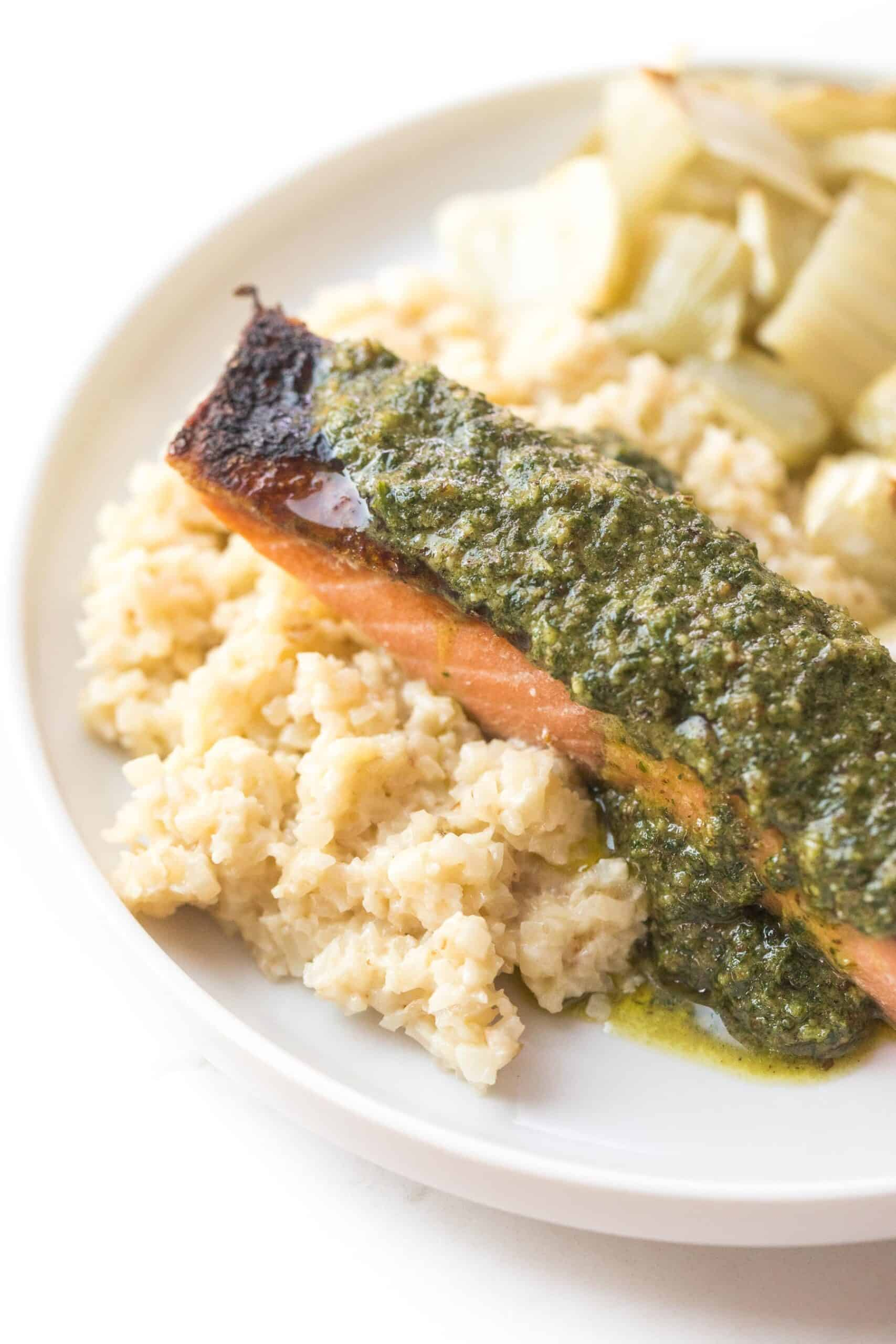 salmon topped with a green sauce on a white plate and background
