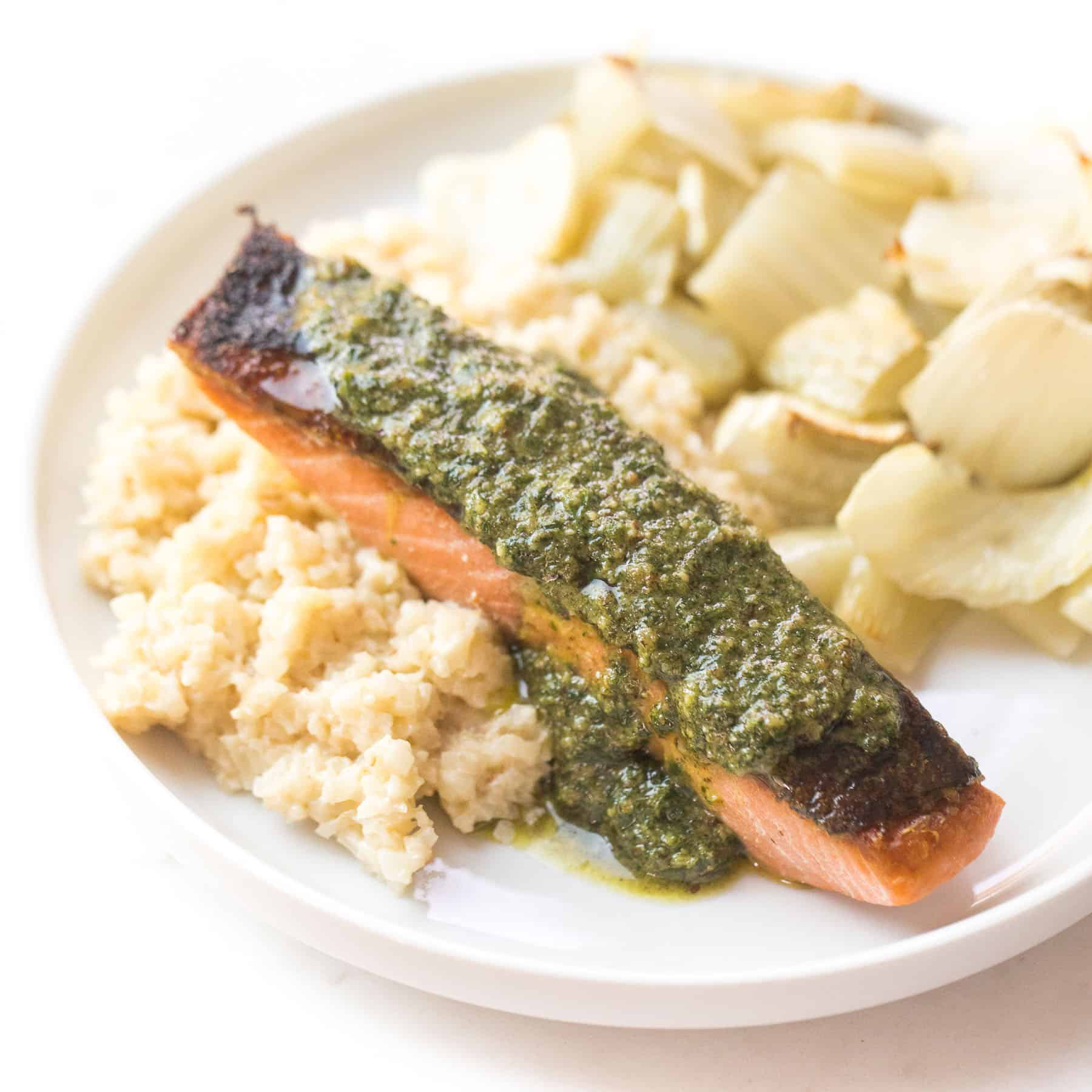 salmon with orange parsley sauce on a white plate with cauliflower rice