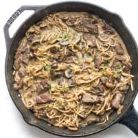 keto beef stroganoff in a cast iron skillet on a white background