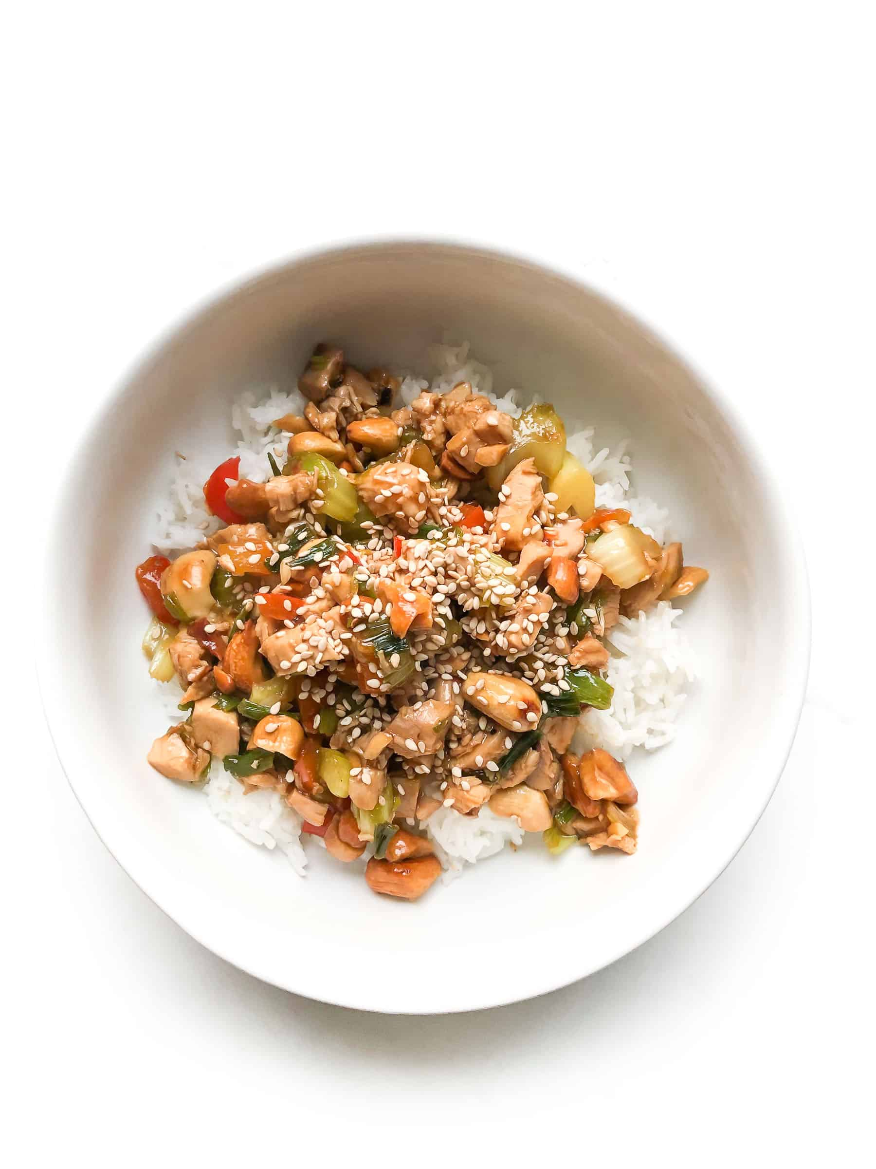 CHICKEN AND CELERY STIR FRY IN A WHITE BOWL TOPPED WITH SESAME SEEDS OVER CAULIFLOWER RICE