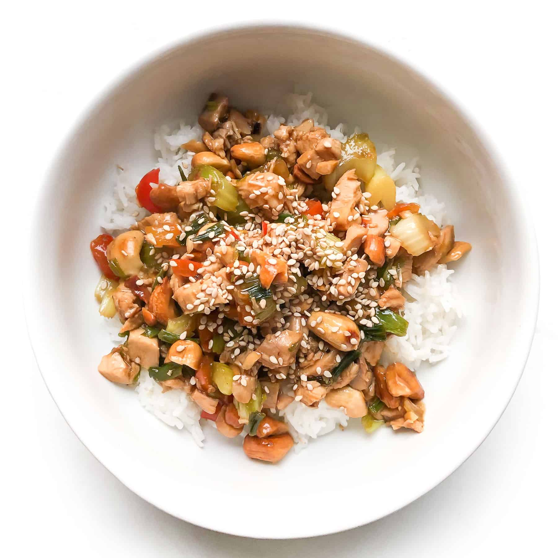 CHICKEN AND CELERY STIR FRY IN A WHITE BOWL TOPPED WITH SESAME SEEDS OVER CAULIFLOWER RICE IN A WHITE BOWL AND BACKGROUND