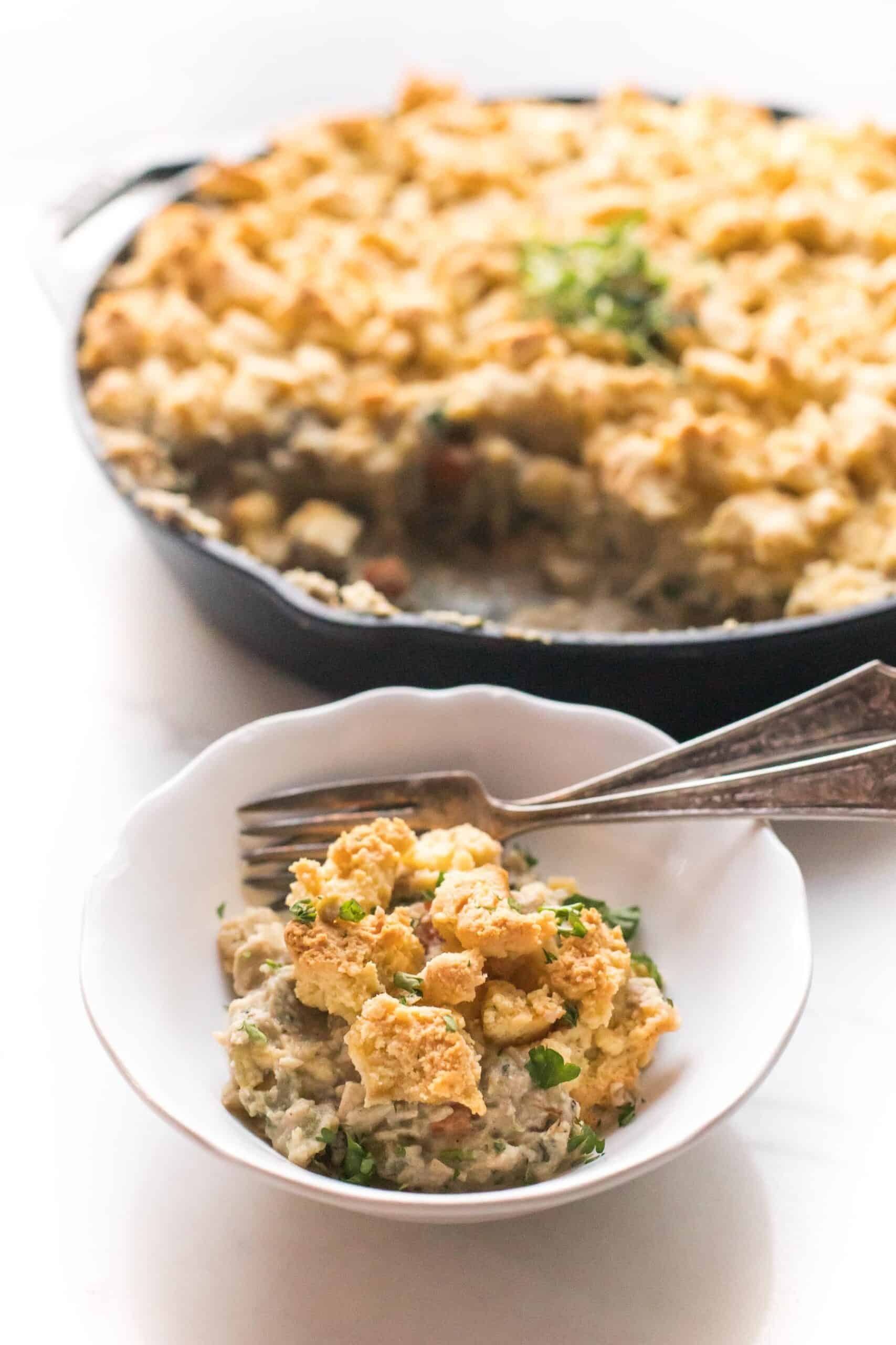 keto chicken pot pie crumble in a cast iron skillet and white bowl on a white background