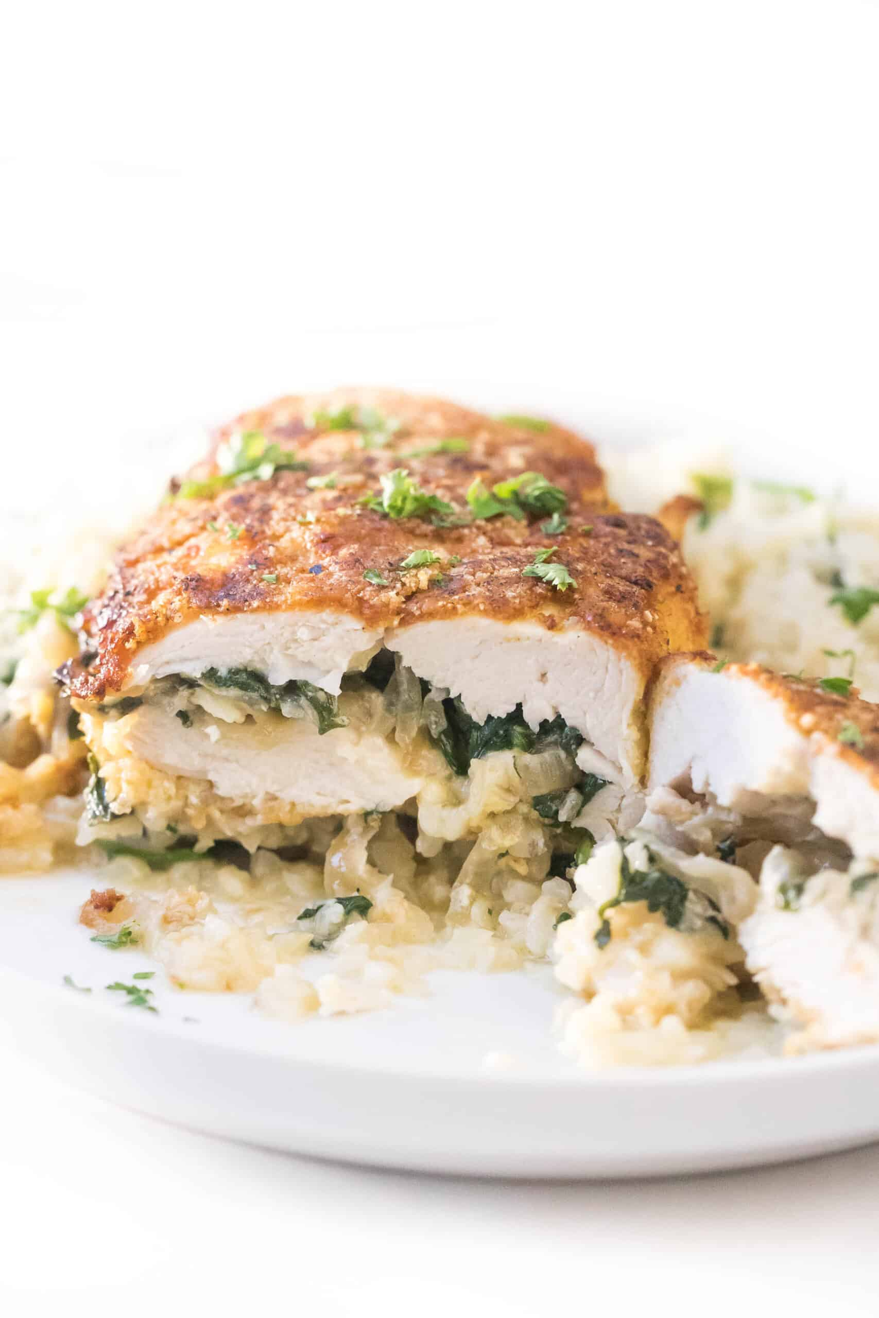 keto brie + spinach stuffed chicken breast cut in half on a white plate with cauliflower rice