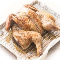 spatchcock roasted chicken with golden brown skin on a rimmed baking sheet