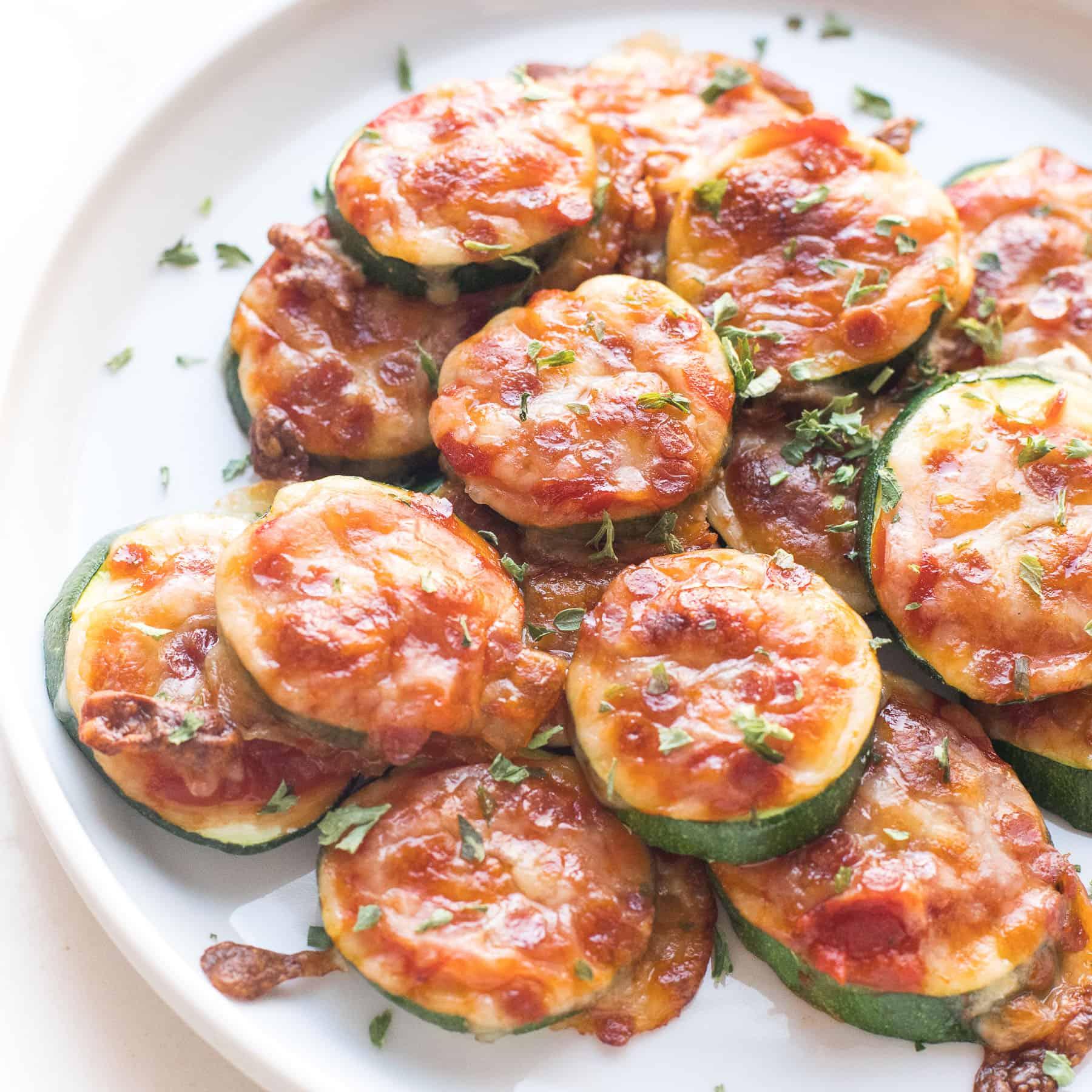 keto mini zucchini pizza bites on a white plate and background