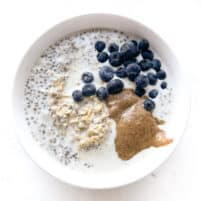 Oatmeal in a white bowl with nut butter and blueberries
