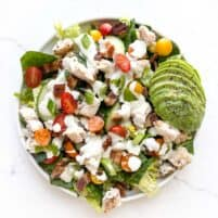 Salad topped with ranch dressing, chicken, avocado, tomatoes, bacon.