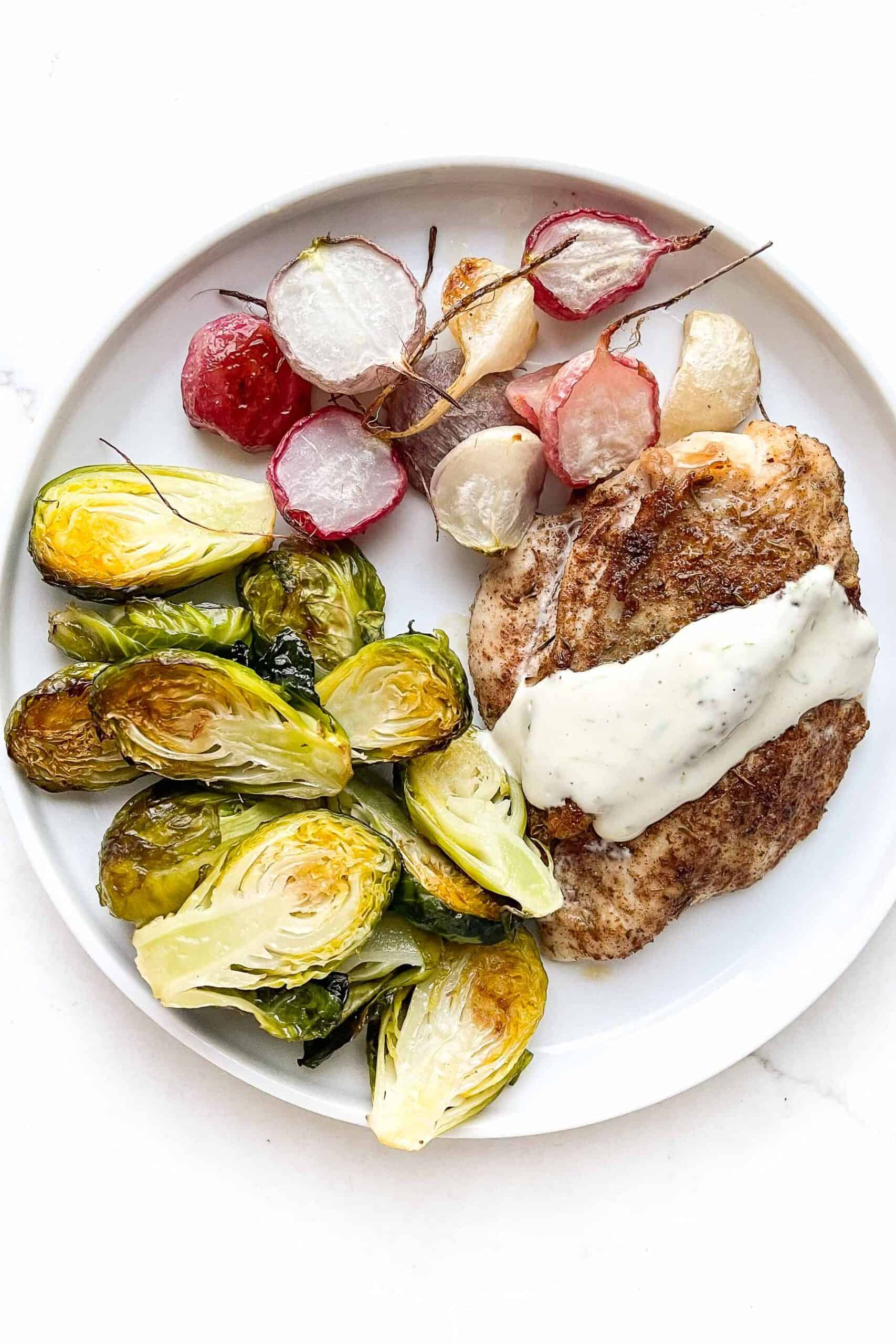 Jerk seasoned chicken breast topped with garlic lime aioli, roasted brussels sprouts + roasted radishes on a white plate and background