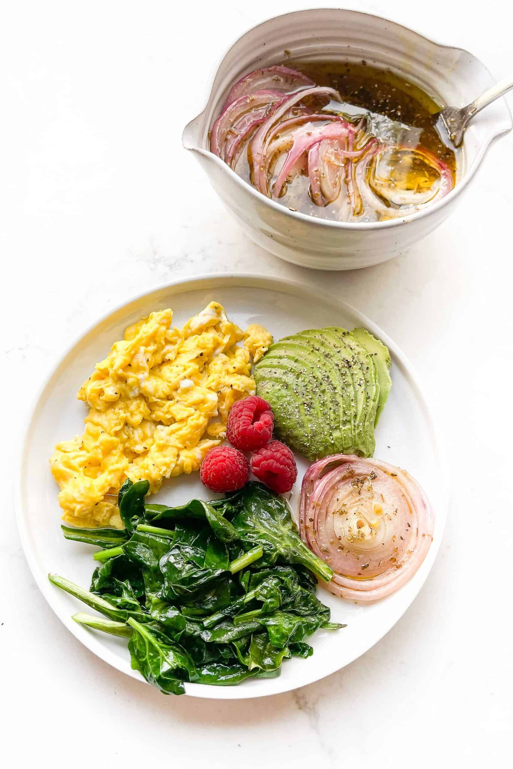 scrambled eggs, sauteed spinach, avocado, red onion and raspberries on a white plate and background