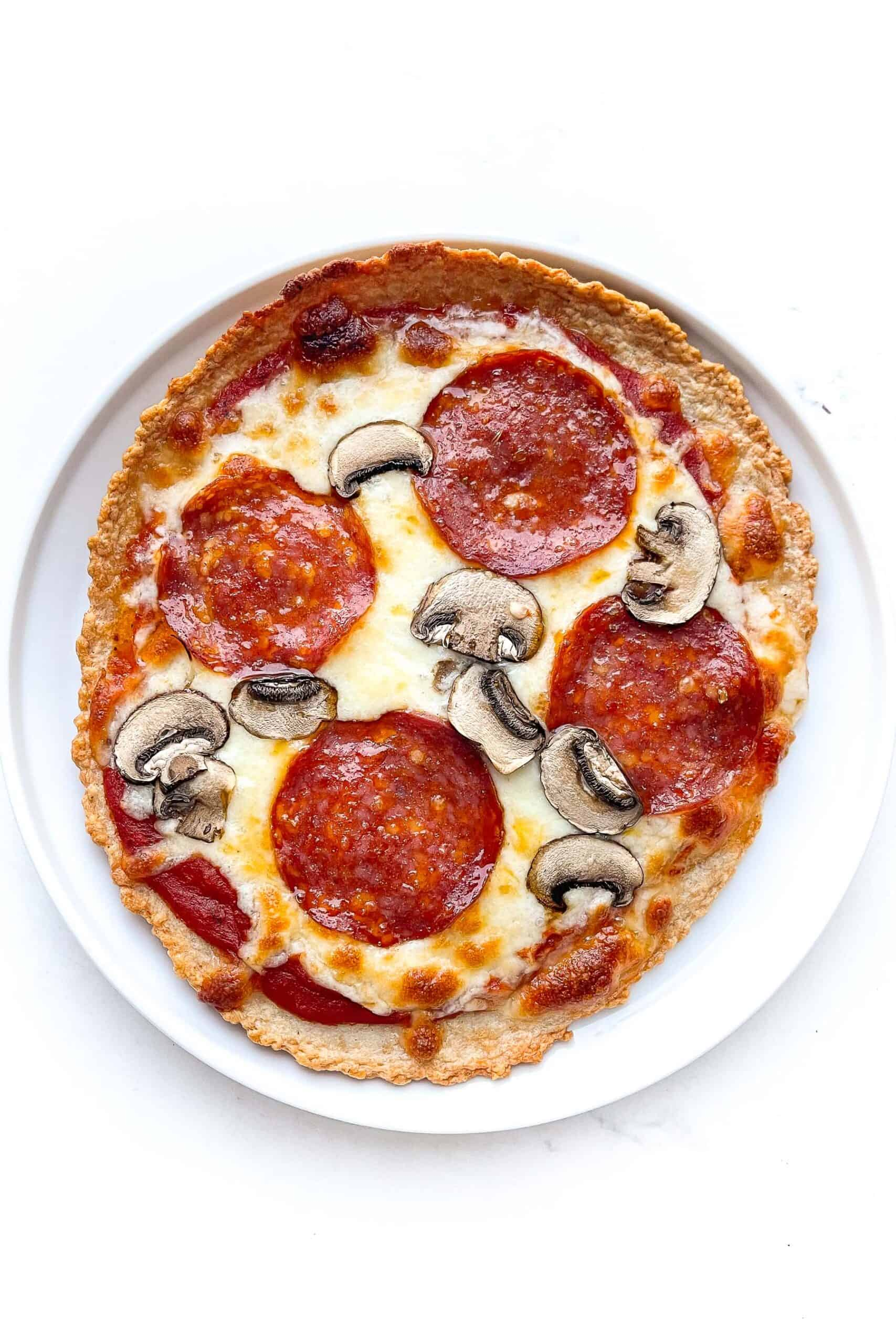 zero carb pepperoni and mushroom pizza on a white plate and background