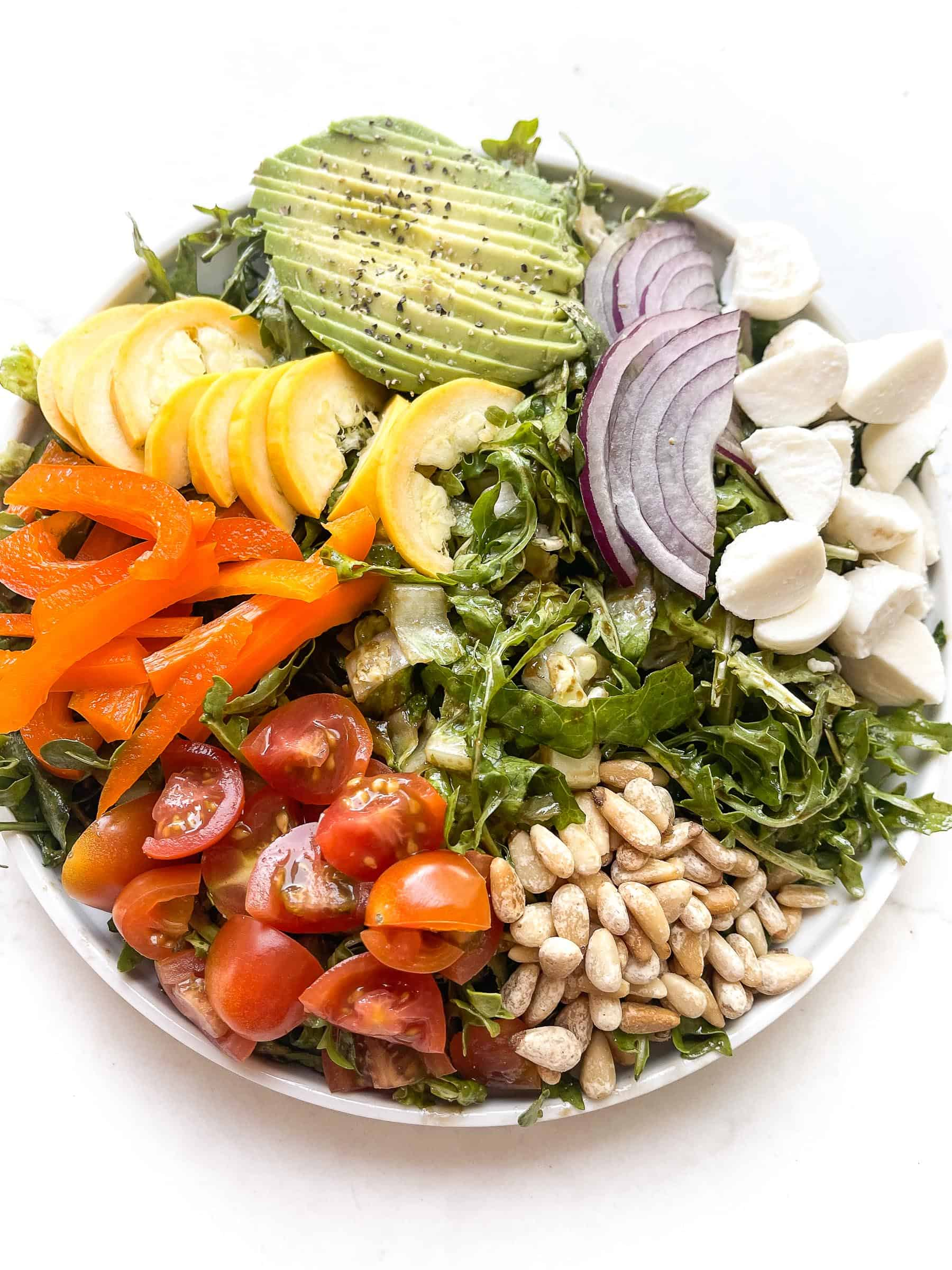 rainbow chopped salad with tomatoes, bell pepper, squash, avocado, red onion, mozzarella + pinenuts over arugula