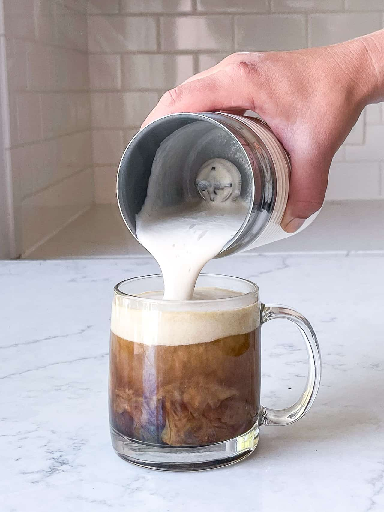 pouring frothed milk into coffee