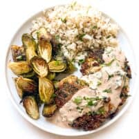 keto southwest tuna cakes topped with sauce on a white plate and background with roasted brussels sprouts and cauliflower rice