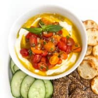 Whipped ricotta dip in a white bowl topped with grape tomatoes, basil and olive oil with cucumbers and crackers