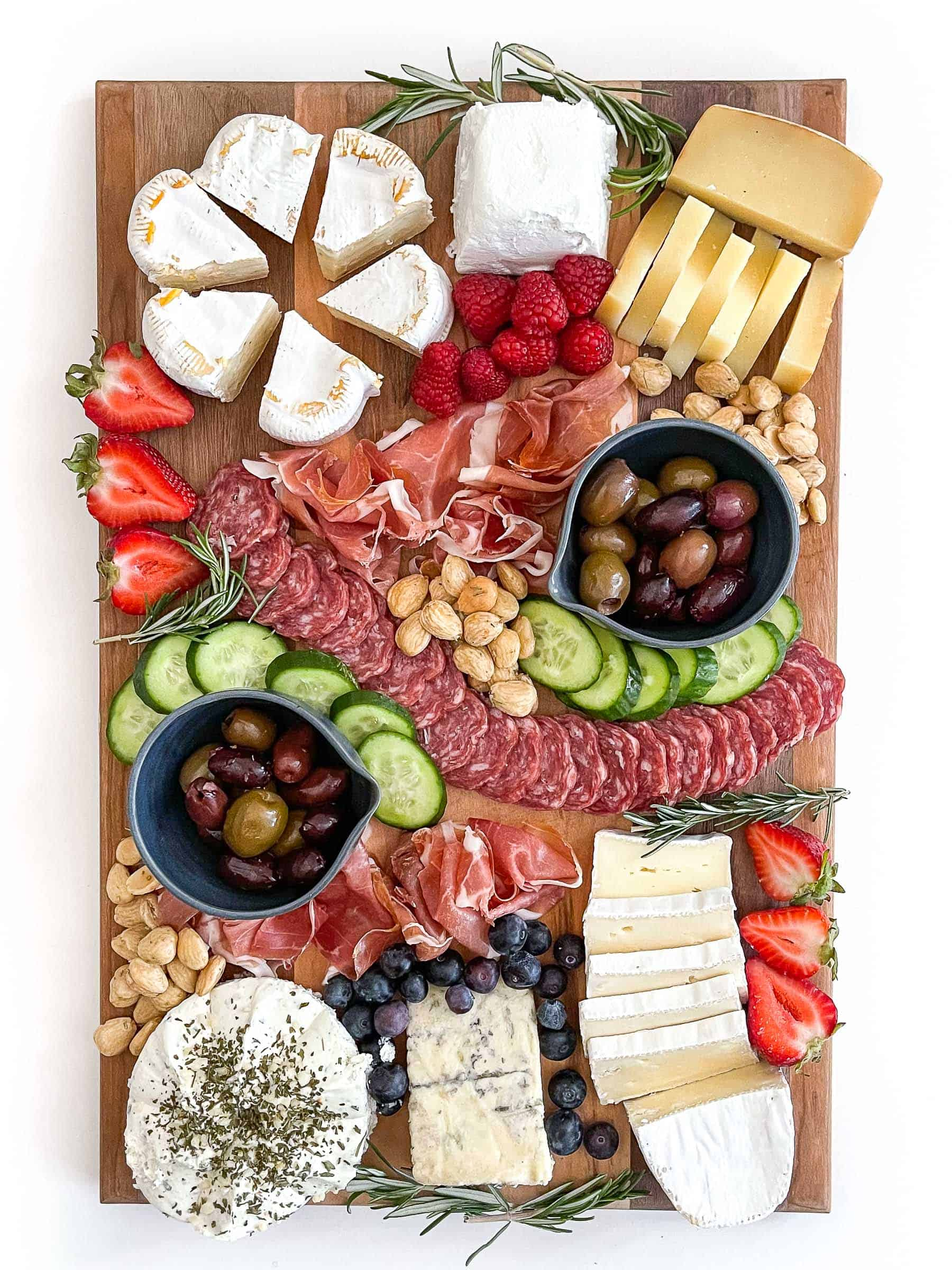 Keto friendly cheese board with sliced cheese, salami, cucumber, nuts, olives and berries