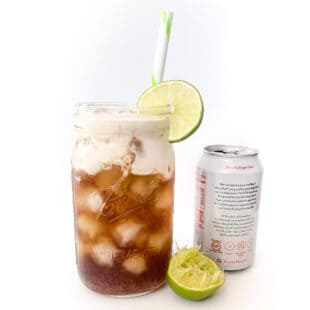 mason jar full of soda topped with cream with a straw and lime garnish on a white background