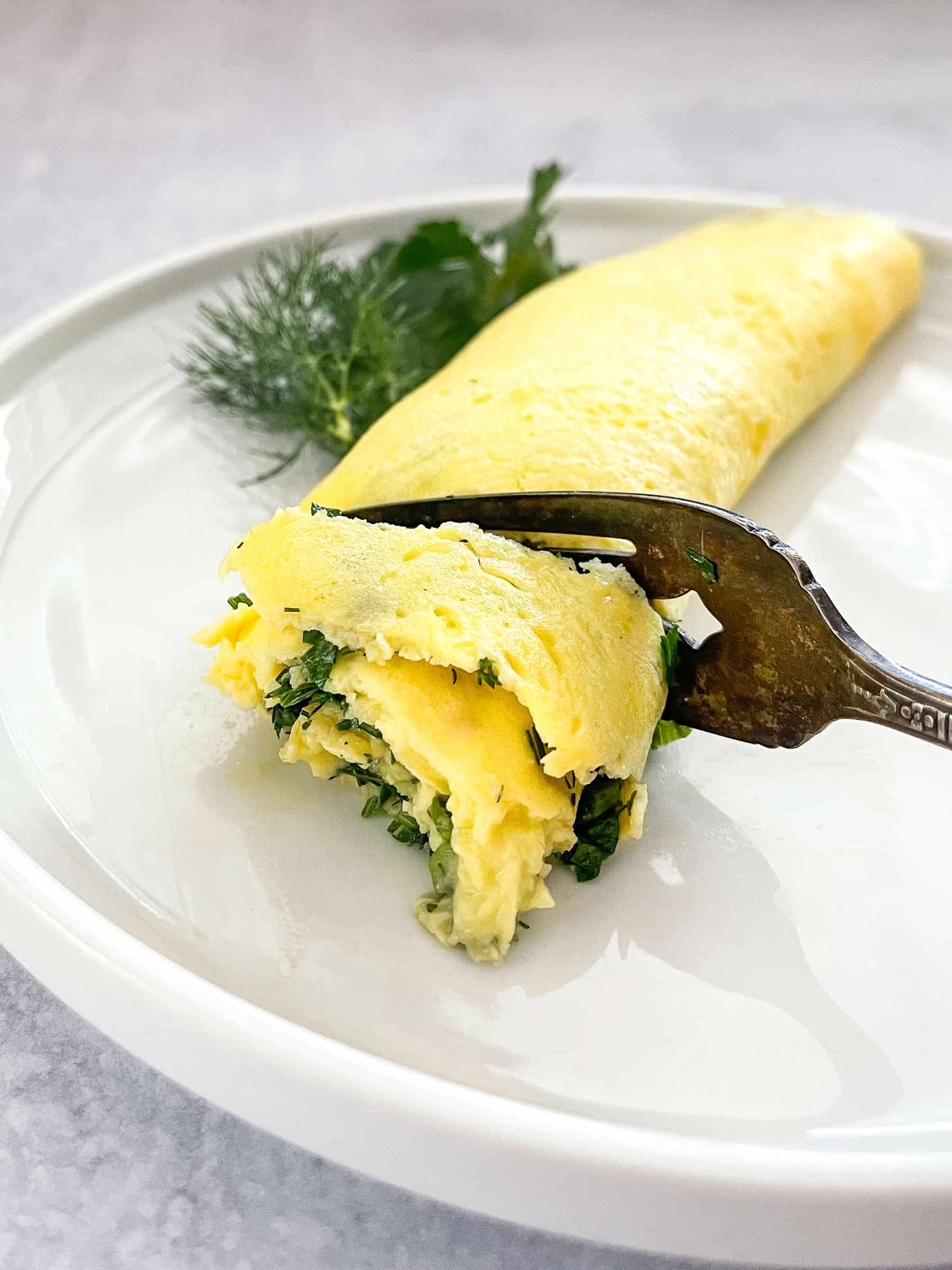 french omelet on white plate garnished with dill and parsley with antique fork cutting omelet
