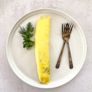 french omelet on white plate garnished with dill and parsley with two antique forks