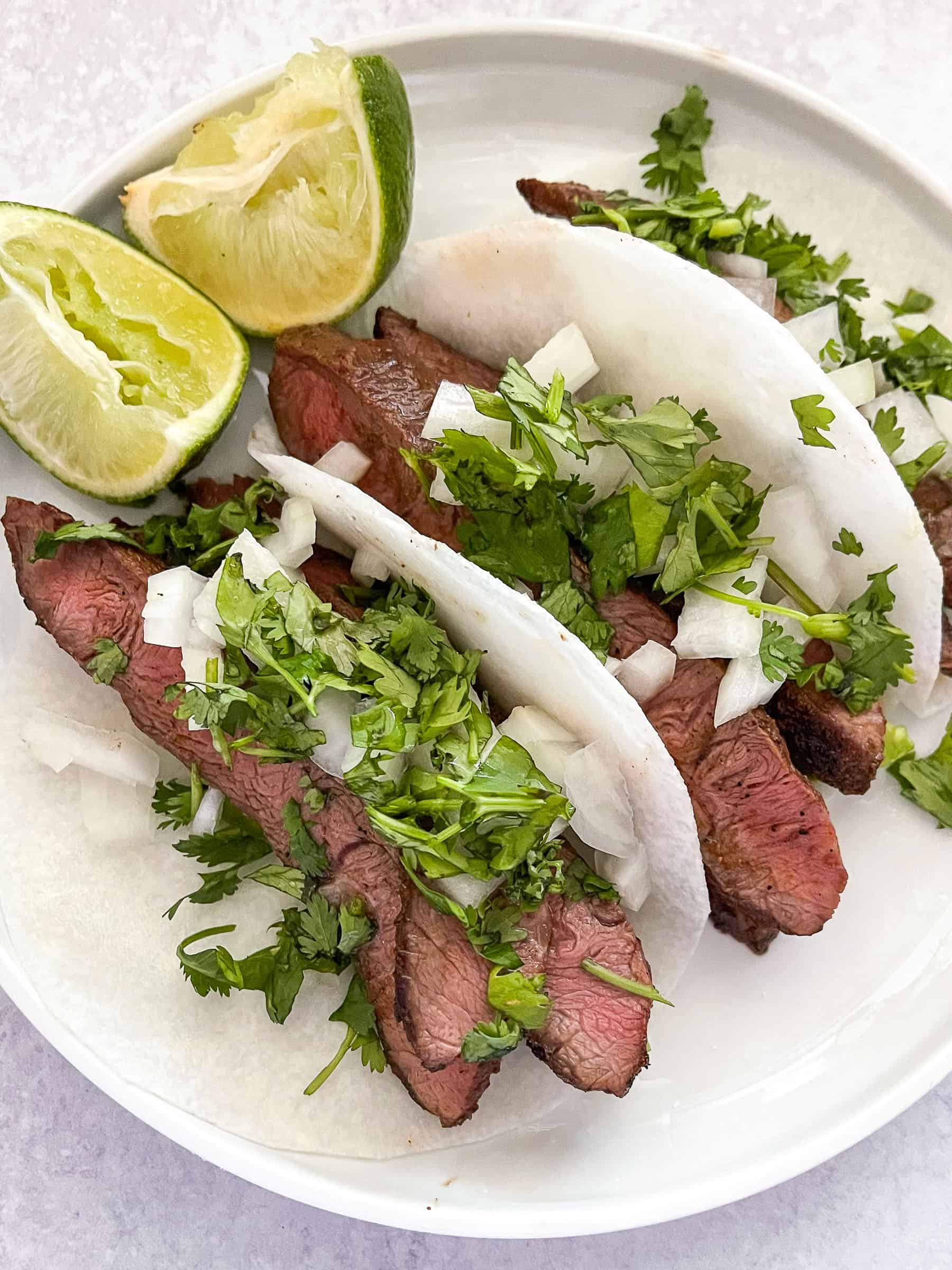 steak tacos on jicama wrap on a white plate with lime and a white background