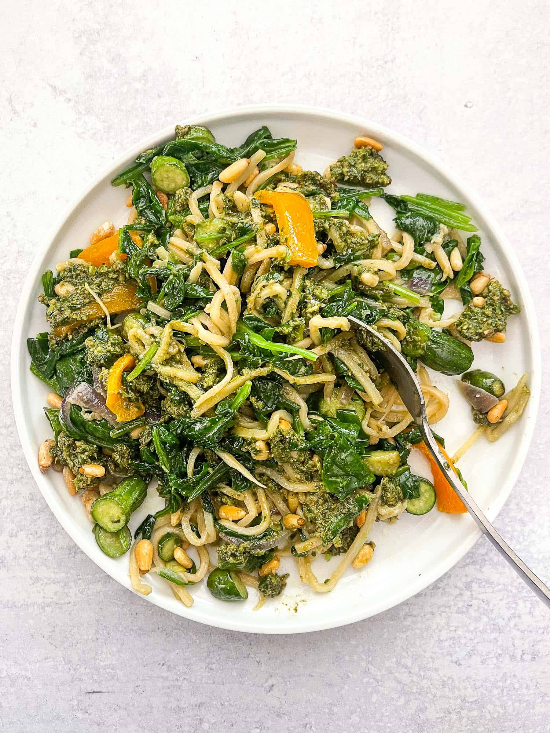 keto summer pasta with pesto on a white plate and background with a silver spoon