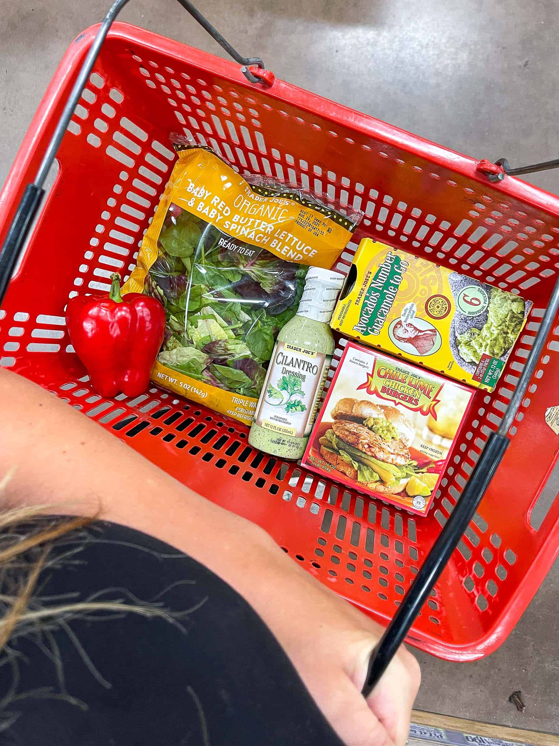 red shopping basket with red bell better, organic lettuce blend, cilantro dressing, guacamole, and chile lime burgers